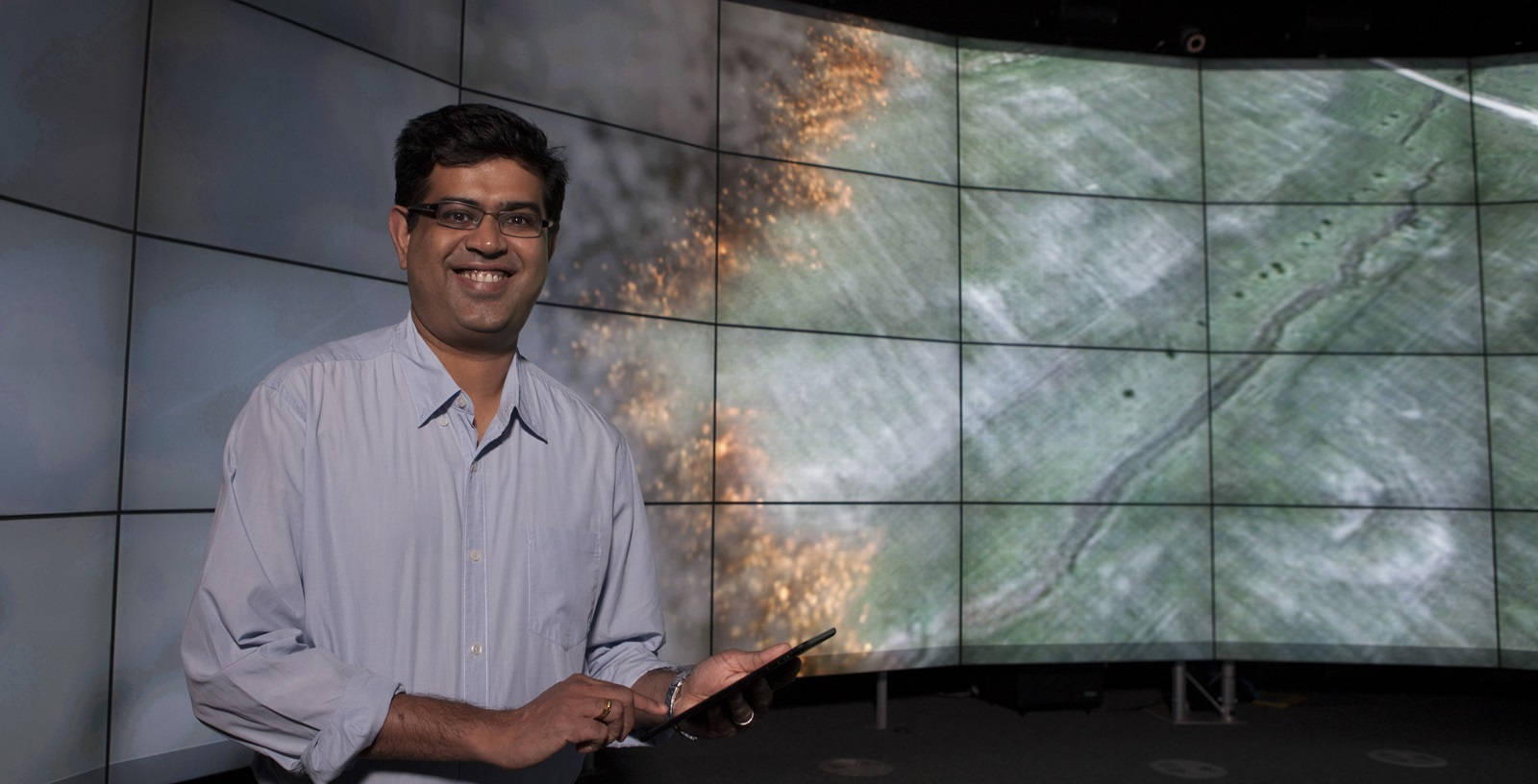 Dr Mahesh Prakash holding a computer tablet in front of a bank of screens showing Sparks software in use.