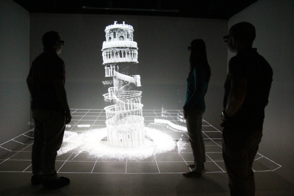 Shadows of three people standing infront of projection of 3D scan of Leaning Tower of Pisa