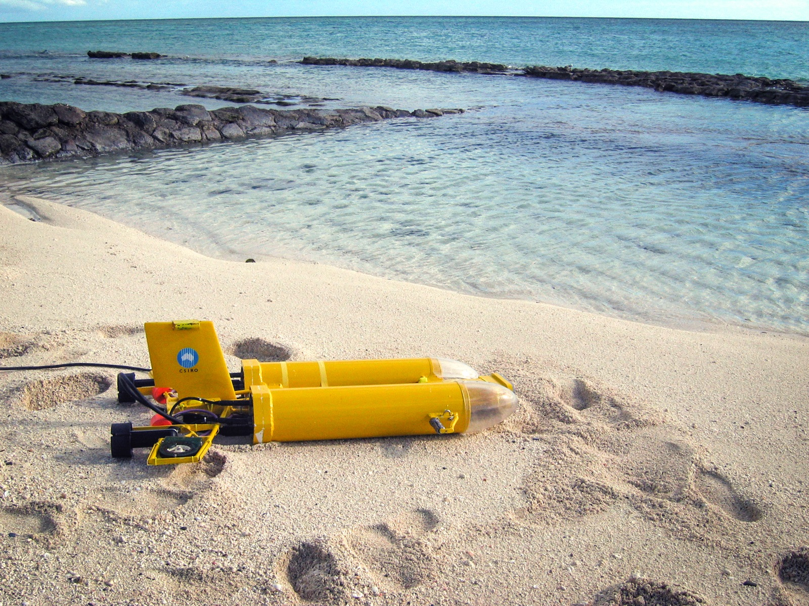 Yellow twin hull autonomous submarine sitting on beach near clear blue water