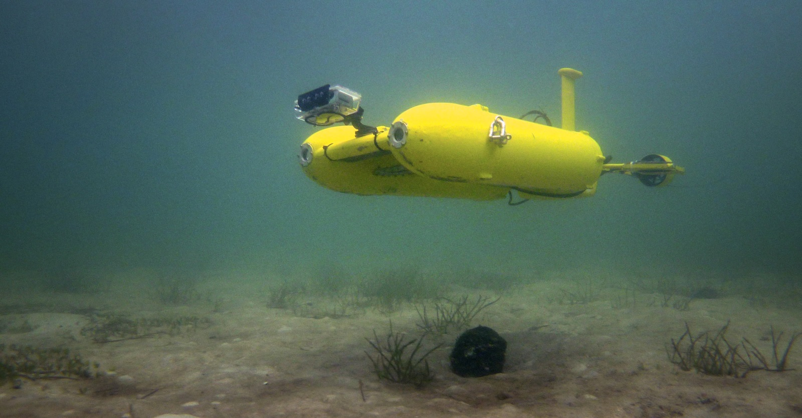Yellow twin hulled autonomous submarine underwater in the ocean