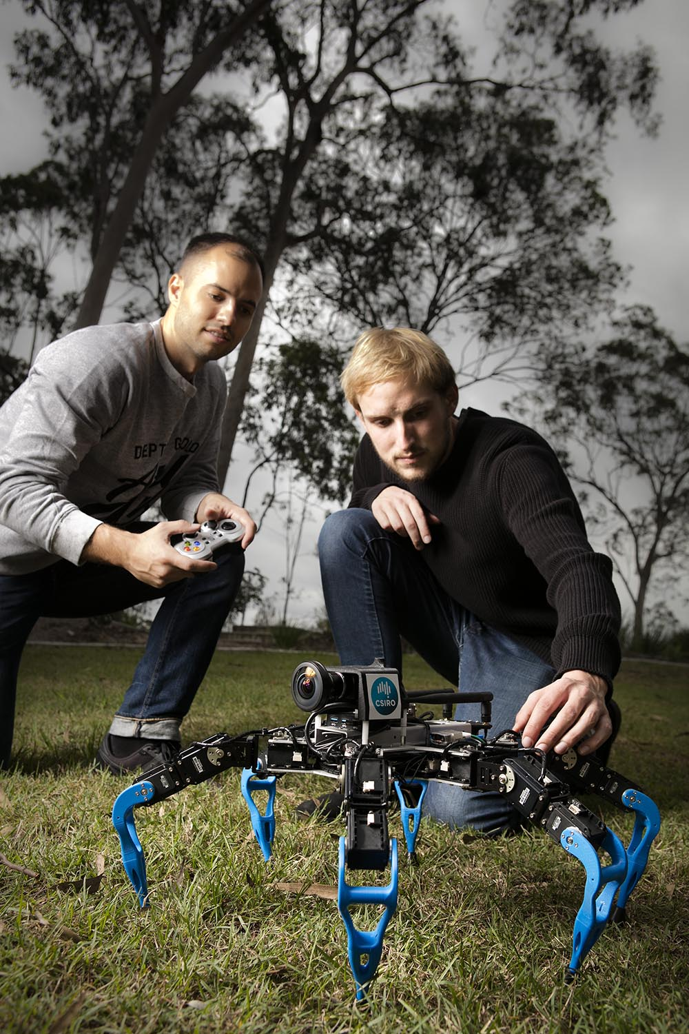 Two people contolling a black spider-like robot with four legs as it walks along the ground.