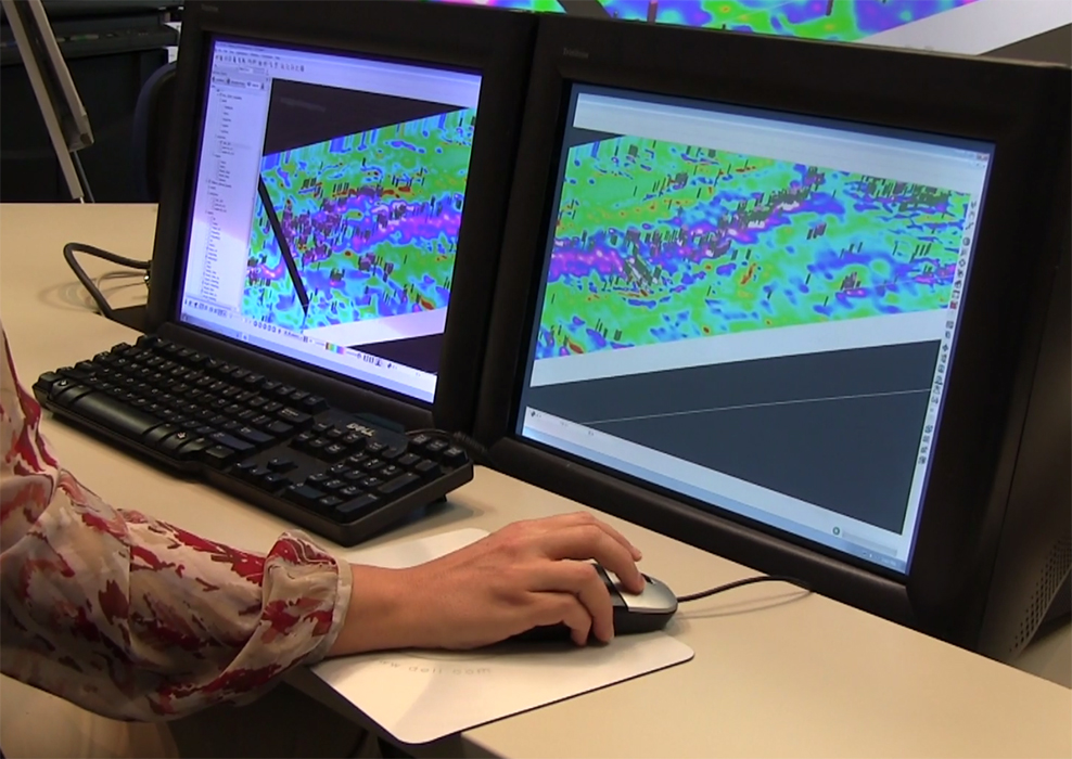 A woman sitting at a dual-screen computer monitor showing geoscience data.