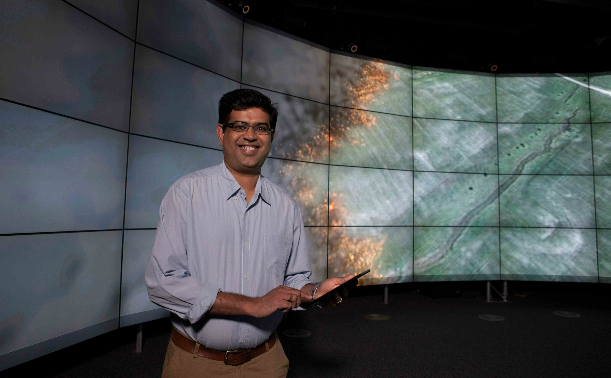 Dr Mahaesh Prakash stands beside a large screen displaying the Spark bushfire modelling tool.