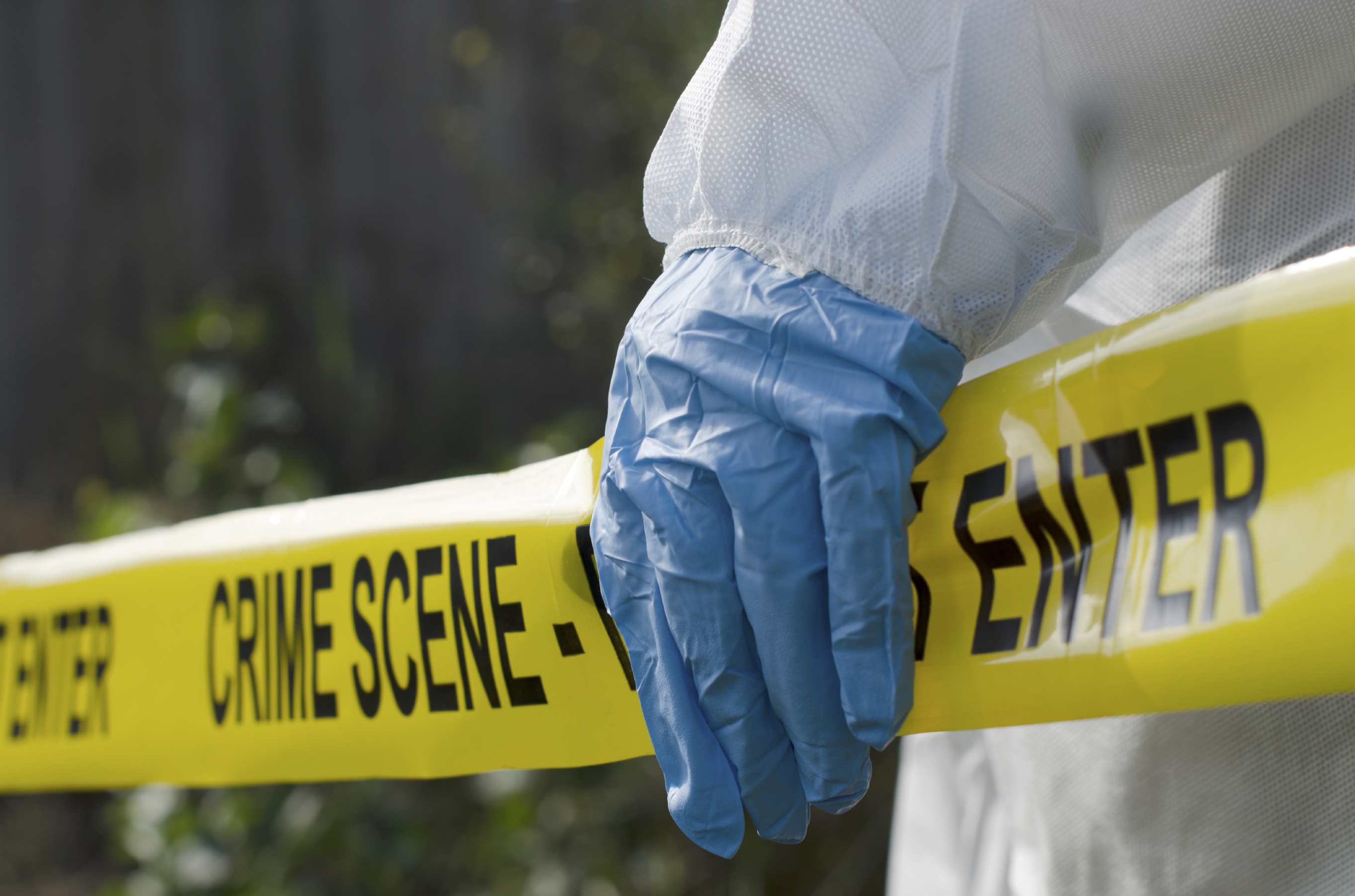 Forensic worker in front of crime scene tape